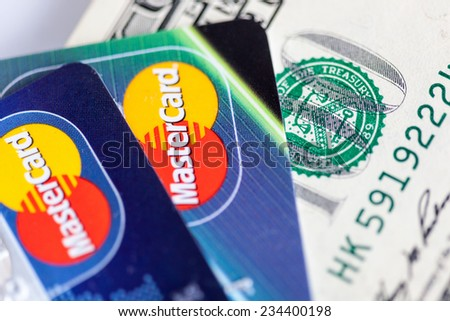 RUSSIA, OREL - 01 DECEMBER 2014: Two credit cards by Mastercard and dollar bills - stock photo