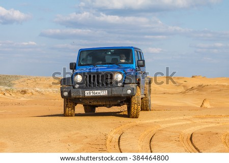 RUSSIA, REPUBLIC OF KALMYKIA, APRIL 22, 2015: blue Jeep Wrangler Rubicon Unlimited at sand dunes near Utta village.