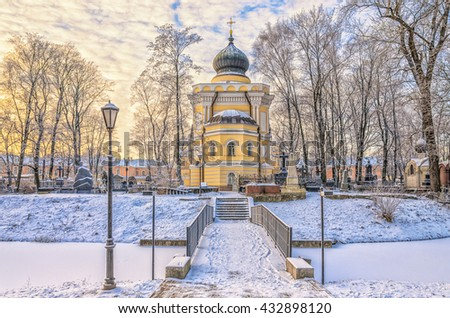 Russia. Saint Petersburg. Alexander Nevsky lavra at a frosty winter day.St.Nicholas church, the cemetery and the bridge over the pond. - stock photo