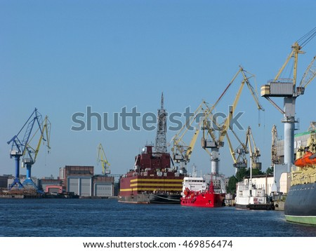 Russia, Saint Petersburg - August 16, 2016: Cargo port with cargo handling cranes, warehouses and ships.