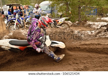 RUSSIA, SAMARA - APRIL 8: Motocross rider A. Nikishkin, slides two wheels and a large slope of a motorcycle in a sharp turn on a sandy road, the Motocross practice April 8, 2012 in Samara, Russia