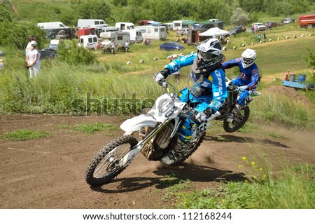 "RUSSIA, SAMARA - JUNE 16: Motocross two unknown racer on a motorcycle the turns on a mountain slope with slip the Cup of Russia in motocross, the class of ""veterans"" on June 16, 2012 in Samara, Russia"