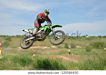 RUSSIA, SAMARA - JUNE 16: MX rider N. Krasilnikov on a motorcycle flying through the air against the sky and mountains, the Regional Motocross Championship on June 16, 2012 in Samara, Russia - stock photo