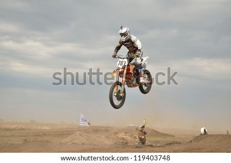 RUSSIA, SAMARA - MAY 6: High Jump through the hill lands MX racer D. Vintaev on a motorbike on a background of dark clouds, the Open class the Regional Motocross on May 6, 2012 in Samara, Russia - stock photo