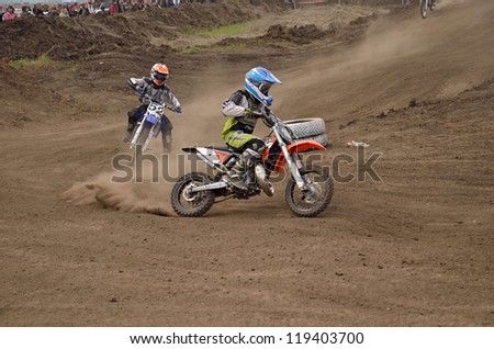 RUSSIA, SAMARA - MAY 6: Youngest participant the MX 104 N. Kornev, 52 B. Forvazov on departure from the turning, the 65 sm3 class the Regional Motocross Championship on Mau 6, 2012 in Samara, Russia - stock photo