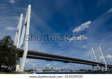 Russia, St. Petersburg. Cable-stayed bridge across the river Neva, a beautiful blue sky with clouds.