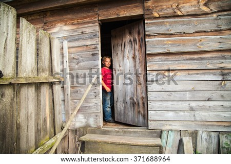Russia. Tambov. Region. Outback. A young boy, a teenager in jeans and a red T-shirt out of an old abandoned wooden house in the village. - stock photo