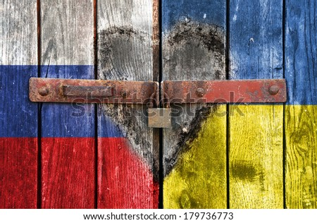 Russian and Ukrainian flag on the background of old locked doors and heart below
