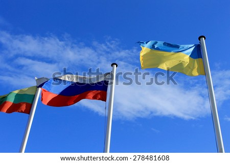 Russian and Ukrainian flags together in blue sky background