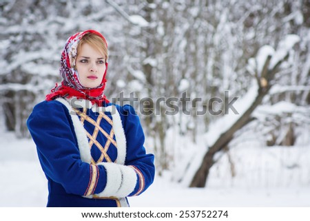 Russian beauty woman in traditional clothes against winter landscape - stock photo
