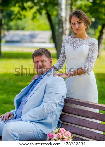 Russian Bride and russian groom sitting in a summer park on a bench