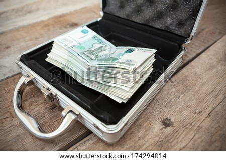 Russian cash money in order inside of steel case, on wooden floor - stock photo