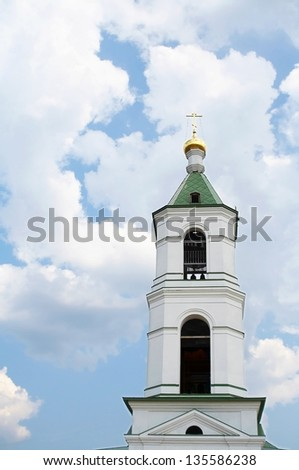 Russian church traditional bell tower with gold cross over blue clouded sky