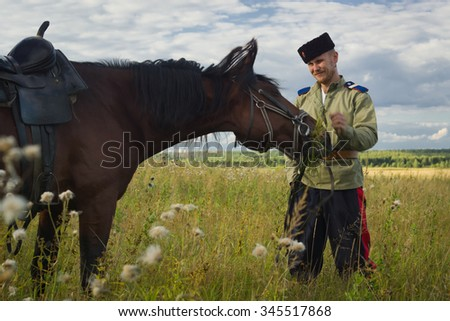 Russian Cossack and a horse resting in the summer field - stock photo