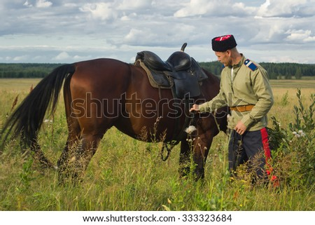 Russian Cossack and a horse resting in the summer field. Day lighting - stock photo