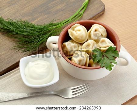 Russian dumplings - pelmeni, in white bowl with sourcream - stock photo