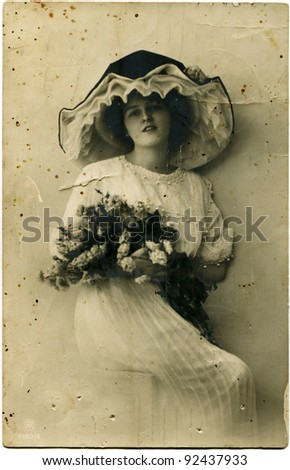 RUSSIAN EMPIRE - CIRCA 1914: Reproduction of antique postcard shows woman in a hat holding a bouquet of flowers, circa 1914
