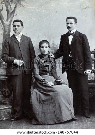 RUSSIAN EMPIRE - CIRCA 1910:Vintage photo shows three young friends wearing elegant clothing. Nostalgic picture. Circa 1910. Russian Empire, beginning of 20th century.