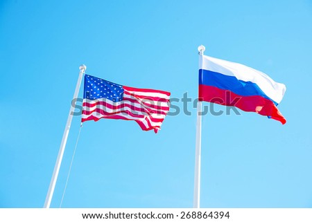 Russian Federation and USA United States of America flags on a blue sky background. idea of the sanctions war combat negotiation and confrontation - stock photo