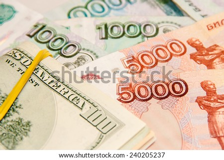 Russian five thousand and one thousand ruble banknotes along pack of one hundred dollars