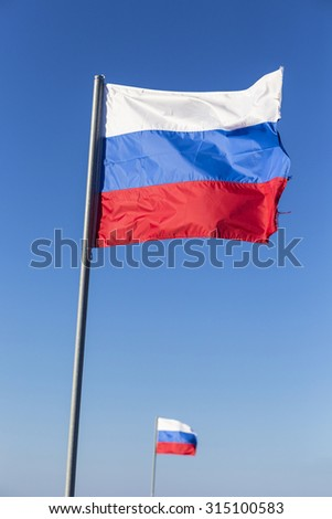 Russian flag, growing in the wind with blue sky as background