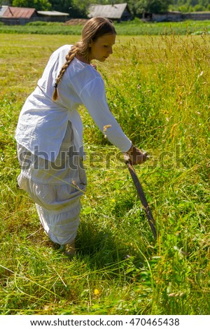 Russian folk girl in a white dress with a long scythe in a field in the village mows