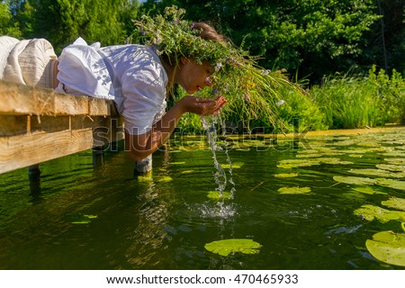 Russian folk girl in a white dress with a long scythe with a wreath on his head in the village on the lake drinking water and washing his face