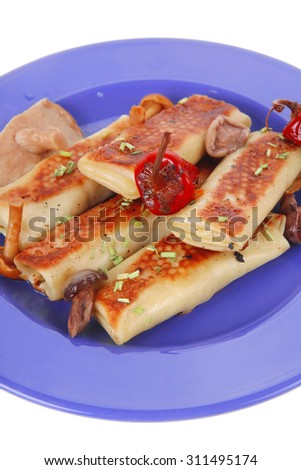 russian food - meat wrapped in a pancake with red hot pepper  and pickled mushrooms served on blue plate isolated over white background - stock photo