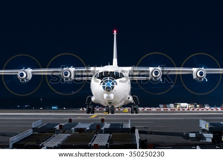 Russian four prop cargo airplane in the dark night - stock photo