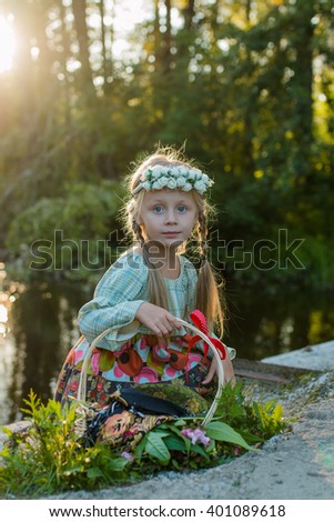 Russian girl in national dress and a wreath of flowers sitting on a summer evening on the banks of the river with a basket in the hands of  - stock photo