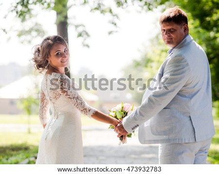 Russian groom and the Russian bride holding hands in the summer the park