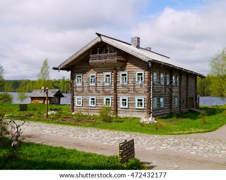 Russian log house between river and road