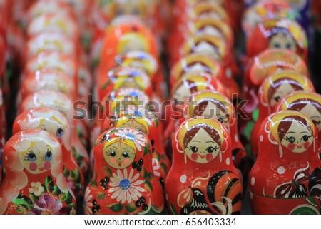 Russian Matroshka - traditional colorful wooden toy dolls on market shelf