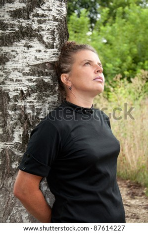 Russian middleaged woman stands of birch