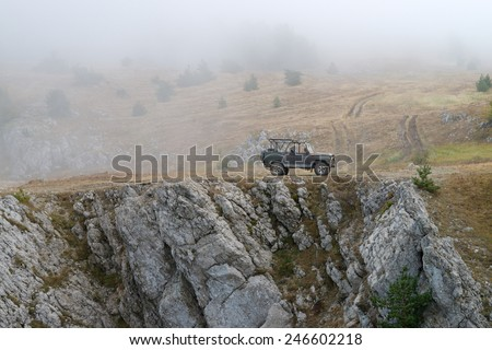 Russian military jeep (UAZ) on the rock in the fog. Vertical pictures.