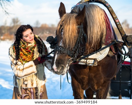 Russian noblewoman in national clothes in the dead of winter in a village near a horse in harness with the sleigh