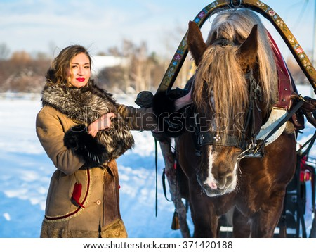 Russian noblewoman in Russian national clothes on a strong frost in the village is close to a horse