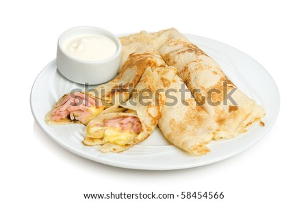 Russian pancakes stuffed by sliced ham and cheese. Isolated on white by clipping path.