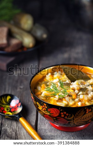 Russian pickle vegan soup in traditional bowl with khohloma paintings served in rustic style - stock photo