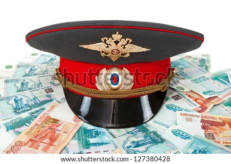 Russian police officer cap on the batch of banknotes - stock photo
