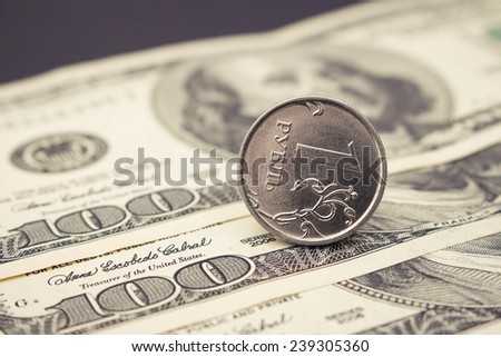 Russian ruble on the background of hundred dollar. Inverted coin. Toned image  - stock photo