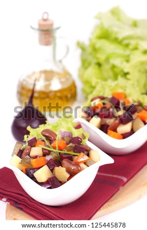 Russian salad vinaigrette served in two small plates on a dark red fabric with small beet and olive oil bottle on the background - stock photo