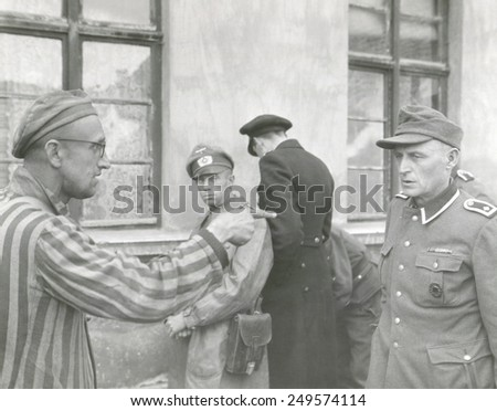 Russian slave laborer points out Nazi guard who brutally beat prisoners. The U.S. Army 3rd Armored Division liberated Buchenwald concentration Camp. April 14, 1945, Germany, World War 2. - stock photo