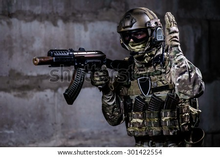 Russian soldier shows special signal with weapon in his hands - stock photo