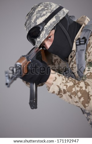 Russian soldier with kalashnikov machine gun aiming or shooting - shot in studio over grey background