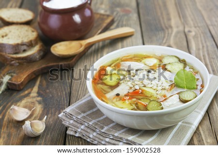 Russian soup Rassolnik with pickles, barley and sour cream on the table