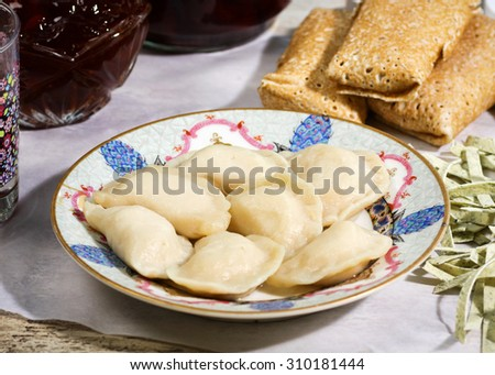 Russian traditional cuisine. Pelmeni meat dumplings with meat stuffed pancakes and homemade noodles on a vintage crockery