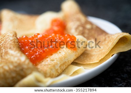 Russian traditional pancake with red caviar - stock photo