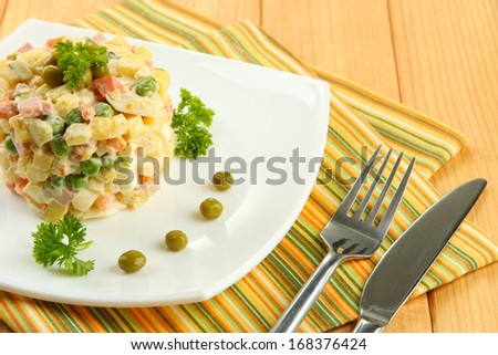 Russian traditional salad Olivier, on color napkin, on wooden background
