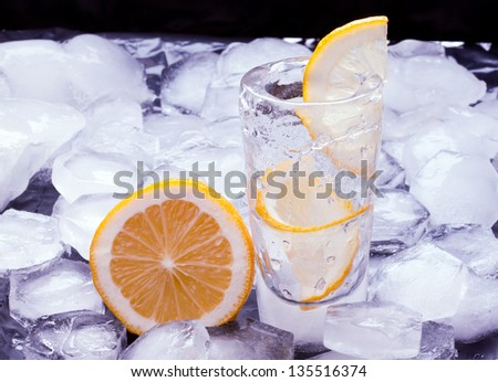 Russian vodka with lemon poured in a glass made of ice